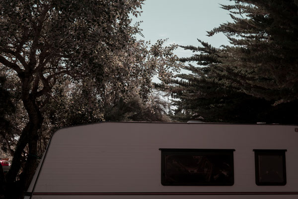 Campingplatz auf der Il de Re - ein Wohnwagen steht unter schattenspendenden Bäumen.