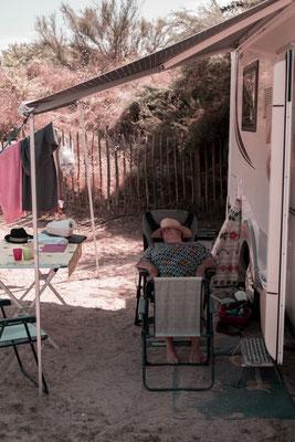 Eine alte Dame macht ein Nickerchen vor ihrem Wohnmobil auf dem Campingplatz auf der Il de Re