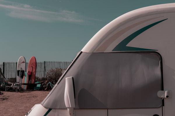 Campingplatz auf der Il de Re  - Wohnmobil mit Sonnenschutz und Surfbrettern im Hintergrund.