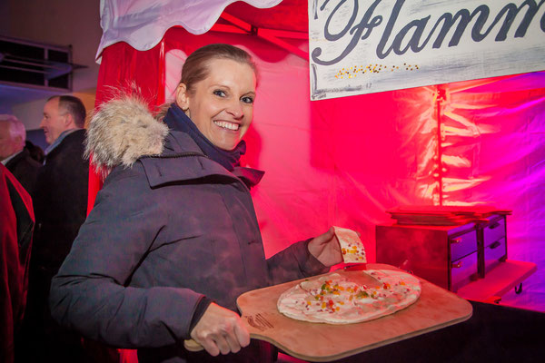 Frau präsentiert glücklich ihren Flammkuchen