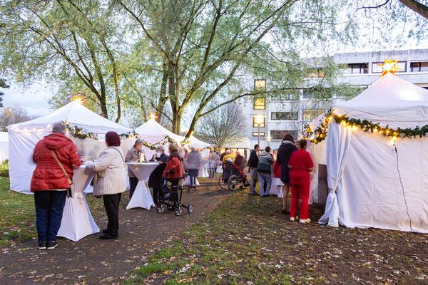 Outdoor Weihnachtsmarkt mit glücklichen Gästen