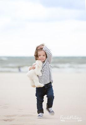 Kleines Mädchen mit Teddybär am Strand