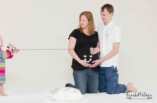 Foto von werdender Mutter mit Babybauch, Geschwisterkind und Vater
