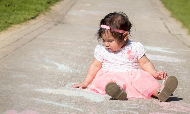 Kleines Mädchen beim spielen auf dem Boden mit entzückendem Kleid