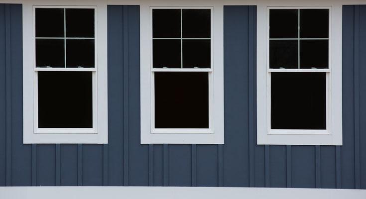 Außenaufnahme von drei Fenster mit blauer Wand