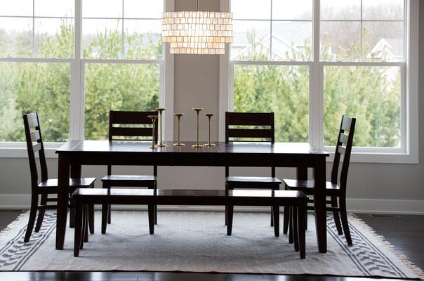 Innenaufnahme von einem modernen Esszimmertisch vor grosser Fensterfront mit Stühlen und cooler Lampe