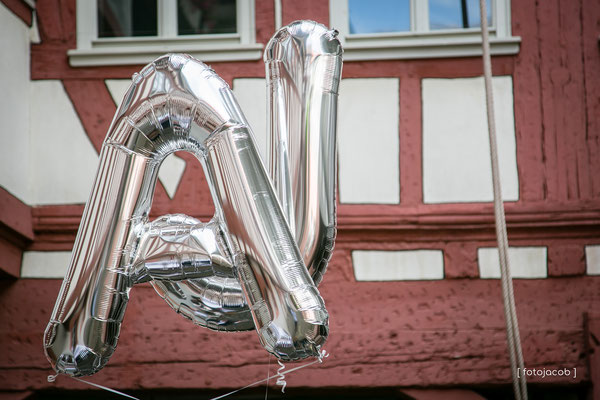 zwei luftballons als ja-wort vor dem fachwerk