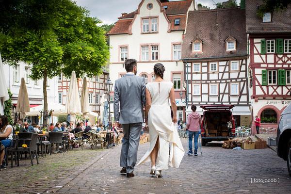 brautpaar geht auf dem markt in weinheim in richtung ulner kapelle