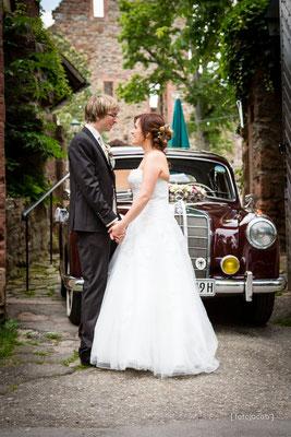 brautpaar stehen sich gegenueber und sehen sich im hintergrund ein mercedes als hochzeitsauto