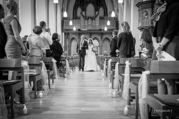 braut wird von ihrem vater in die kirche begleitet