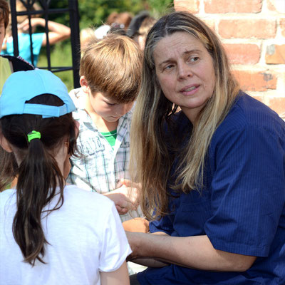 Tierärztin Dr. Herkt inmitten der Kinder des die Storchenstation besuchenden Horts