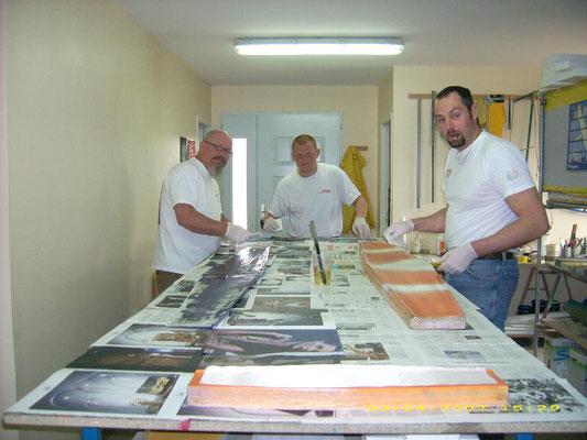 Alexis Maréchal, Tom Copp et Mathieu Mervelet dans l'atelier Aeromod sont en train de stratifier à la résine epoxy