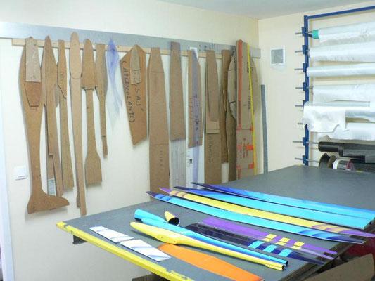 la table de découpe de l'atelier Aeromod avec des gabarits, des rouleaux de tissu de verre et de carbone, et des éléments de planeurs