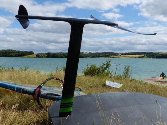winfoil aeromod v2 noir et vert dans l'herbe au lac de la ganguise sur fond de ciel bleu