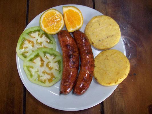 Chorizos (Bratwurst) - eine der leckersten gibts in Santa Rosa, wie im Foto typisch serviert mit Limone, Arepa & Tomatenscheiben