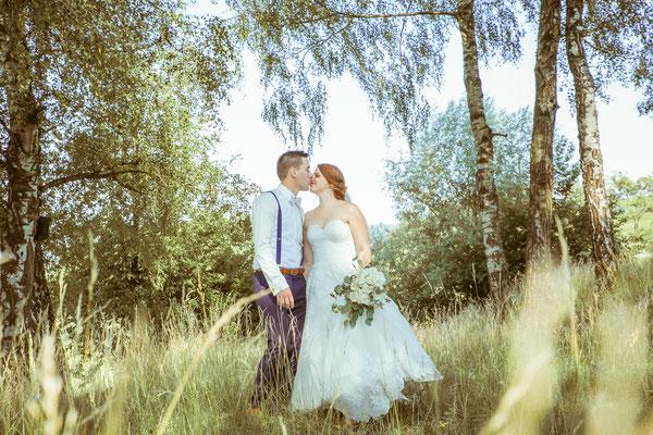 Hochzeitsbild von Anne und Daniel beim Shooting mit Kuss im Feld von Hochzeitsfotograf Timo Erlenwein