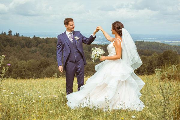 Hochzeitsfoto von Verena und Daniel Bräutigam dreht Braut im Feld fotografiert von Timo Erlenwein Fotografie