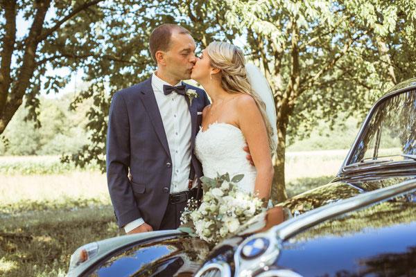 Hochzeit Kerstin und Georg Kuss an Hochzeitsauto fotografiert von Timo Erlenwein Fotografie