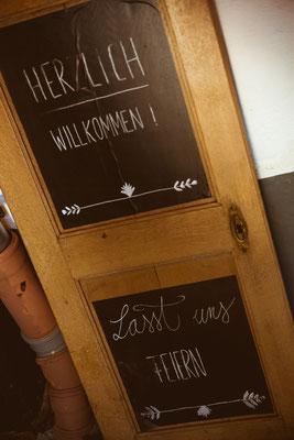 Hochzeitsbild von Julia's und Clemens' Eingangsschild zur Location von Timo Erlenwein Fotografie