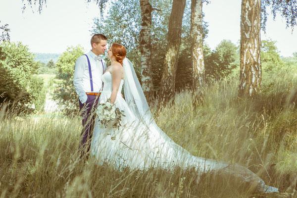 Hochzeitsbild von Anne und Daniel beim Kuss im Feld von Hochzeitsfotograf Timo Erlenwein