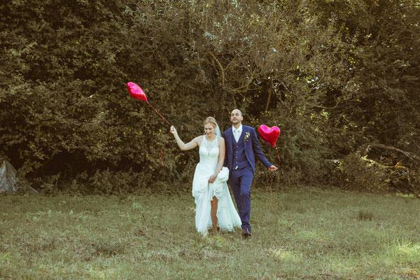 Hochzeitsbild von Julia und Clemens auf einer Wiese in Malterdingen mit Herzluftballons von Timo Erlenwein Fotografie