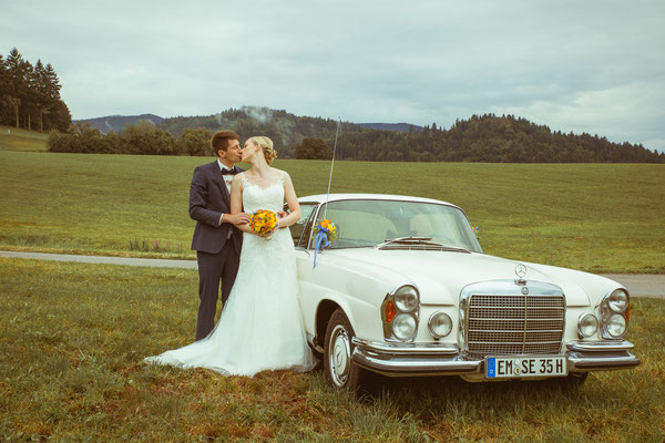 Hochzeitsbild von Susanne und Wolfgang mit Kuss am Hochzeitsauto von Hochzeitsfotograf Timo Erlenwein