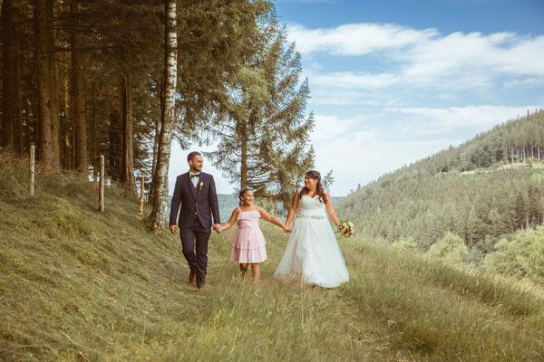 Hochzeit Valerie Simon Brautpaar mit Tochter läuft am Waldrand fotografiert von Timo Erlenwein Hochzeitsfotograf