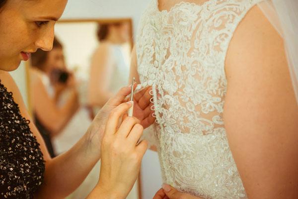 Hochzeitsbild von Anne beim Anziehen des Brautkleides von Hochzeitsfotograf Timo Erlenwein