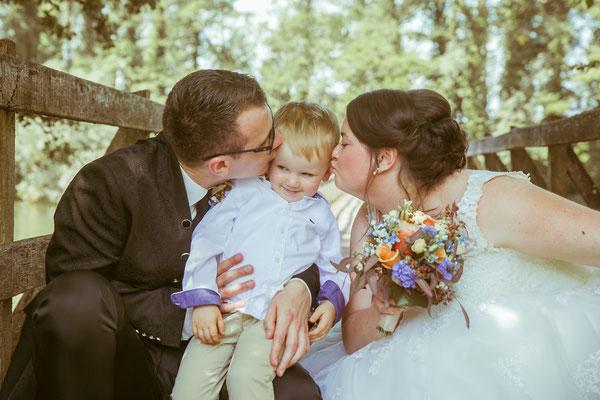 Hochzeitsbild von Jenny und Marius während sie ihren Sohn küssen von Hochzeitsfotograf Timo Erlenwein