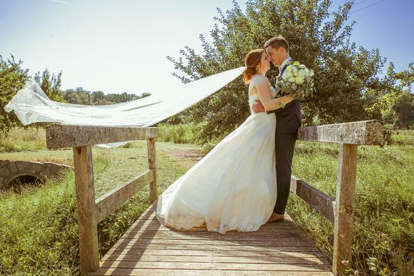 Hochzeitsbild von Anne und Daniel beim Shooting auf der Brücke mit Schleier im Wind von Hochzeitsfotograf Timo Erlenwein