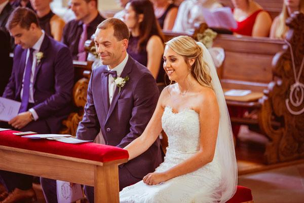 Hochzeit Kerstin und Georg lächelnd und händchenhaltend in Kirche fotografiert von Timo Erlenwein Fotografie