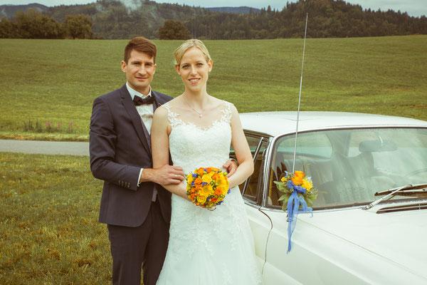Hochzeitsbild von Susanne und Wolfgang am Hochzeitsauto von Hochzeitsfotograf Timo Erlenwein