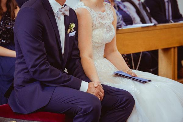 Hochzeitsbild von Anne und Daniel beim Händchenhalten in der Kirche von Hochzeitsfotograf Timo Erlenwein