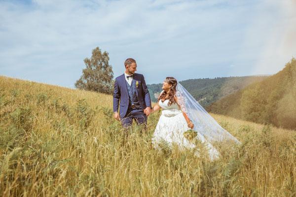 Hochzeit Valerie Simon Shootingbild laufen durch ein Feld fotografiert von Timo Erlenwein Hochzeitsfotograf