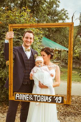 Hochzeitsfoto Anne und Tobi Hochzeitspaar in einem Fotorahmen mit der Tochter fotografiert von Timo Erlenwein Fotografie