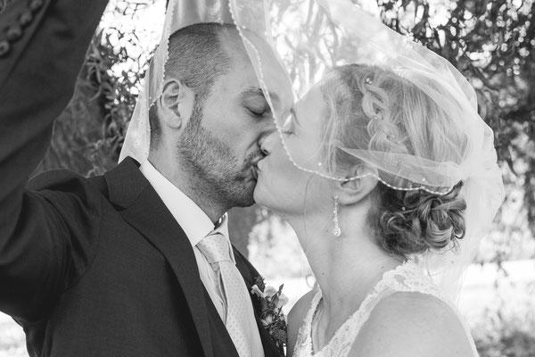 Hochzeitsbild von Julia und Clemens mit Kuss hinter dem Schleier unter einer Weide in Malterdingen von Timo Erlenwein Fotografie