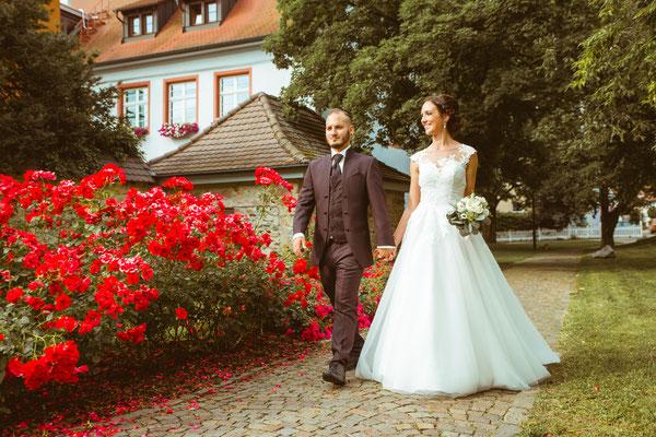 Hochzeitsfoto Alena und Salvatore laufend beim Shooting mit Rosen fotografiert von Timo Erlenwein Fotografie