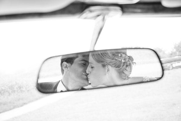 Hochzeitsbild von Susanne und Wolfgang im Rückspiegel vom Hochzeitsauto von Hochzeitsfotograf Timo Erlenwein