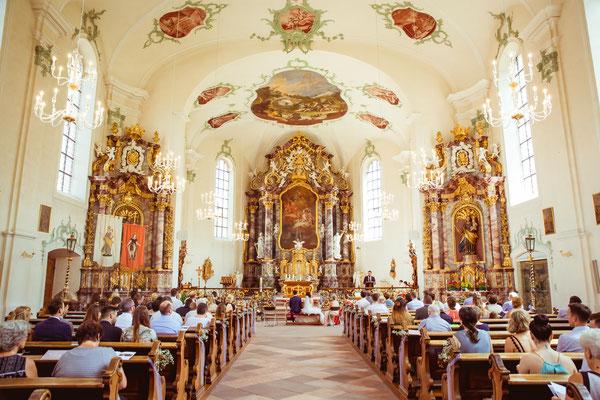 Hochzeitsbild Verena und Daniel in der Kirche von hinten mit der Gesellschaft fotografiert von Timo Erlenwein Fotografie