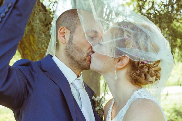 Hochzeitsbild von Julia und Clemens mit einem Kuss hinter dem Schleier von Timo Erlenwein Fotografie