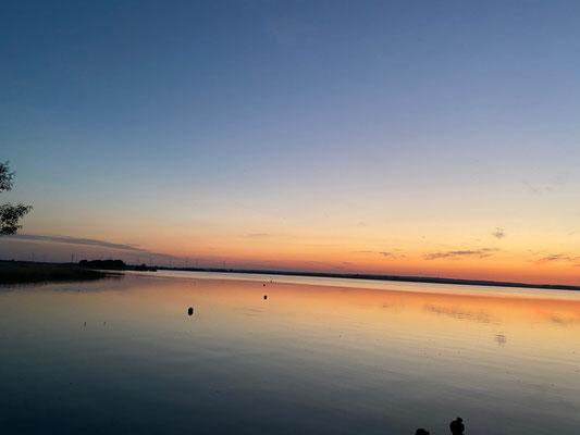 Der Sonnenuntergang färbt den Himmel bunt - der See spiegelt die schönen Farben.