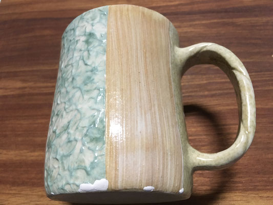 和紙柄アレンジのマグカップ第1号。泥がしっかり定着していなかった部分は衝撃に弱いので剝がれてしまう。底のカド、白く釉薬を塗ってある部分。