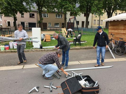 Die Männer bauen das Zelt auf