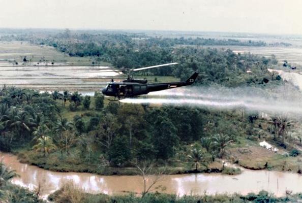 Ein Armeeubschrauber sprayt Agent Orange über Wäldern und Landwirtschaftsland. (Foto U.S. Army).