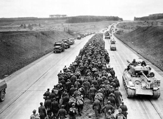 Columnas de vehículos estadounidenses avanzan hacia el interior de Alemania por autopista, mientras miles de prisioneros nazis alemanes marchan hacia la retaguardia, mayo de 1945.