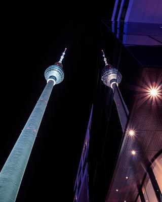 """Spiegelung des Berliner Fernsehturms """"Alex"""" in einem der umliegenden Geschäftshäuser"""