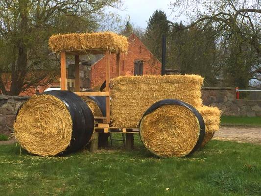 Bild eines Traktors, der aus Stroh modelliert ist.