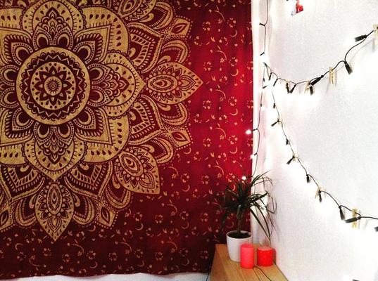 Weinrotes Tuch mit goldener Lotusblüte an der Wand