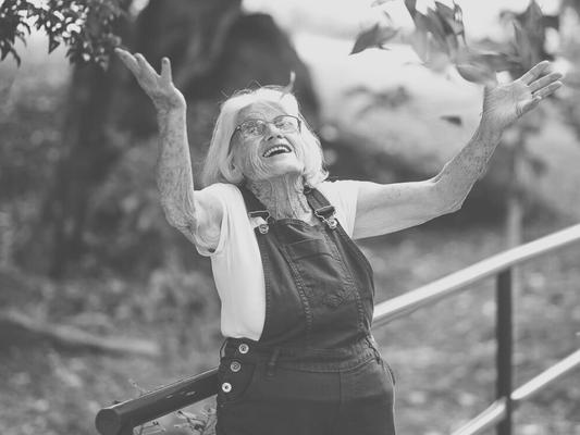 Alte Dame im Garten wirft Laub