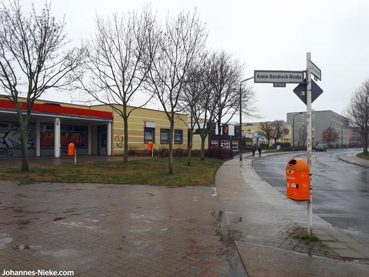 Gebäudeensemble entlang der Louis-Lewin-Straße zwischen Adele-Sandrock- und Albert-Kuntz-Straße mit Kaufhalle, Bäckerei, Spielhalle und Spätkauf, dahinter die modulare Unterkunft für Geflüchtete
